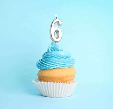 Birthday cupcake with number six candle on blue background Banco de Imagens