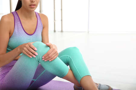 Young woman in sportswear having knee problems at gym, closeup. Space for text Imagens