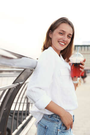 Young woman with refreshing drink on city street 写真素材