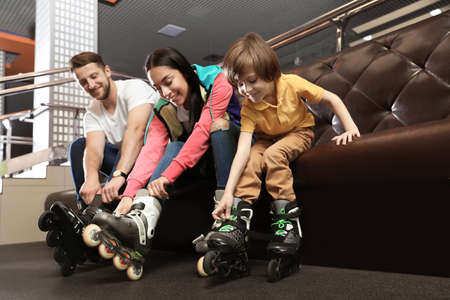 Happy family putting on roller skates indoors 写真素材