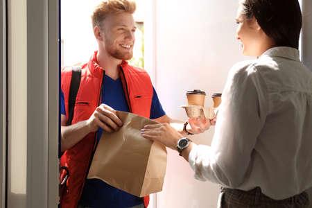 Mensajero dando orden a mujer joven a puerta abierta. Servicio de comida a domicilio