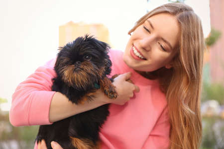 Young woman with adorable Brussels Griffon dog outdoors 写真素材