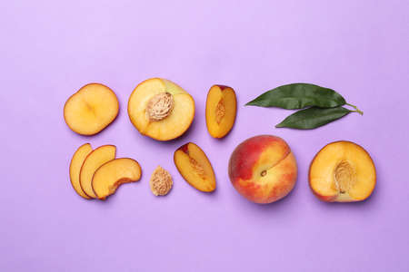 Flat lay composition with sweet juicy peaches on lilac background