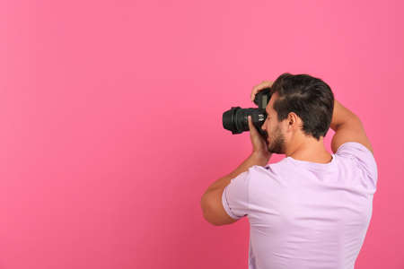 Young professional photographer taking picture on pink background. Space for text 版權商用圖片