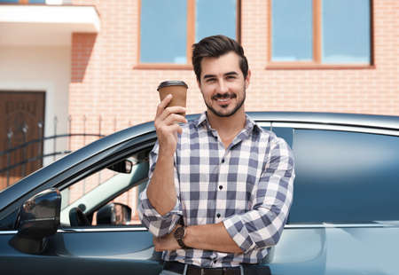 Attractive young man with cup of coffee near luxury car outdoors