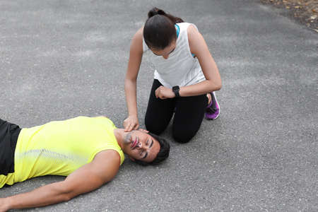Young woman checking pulse of unconscious man on street. Space for text