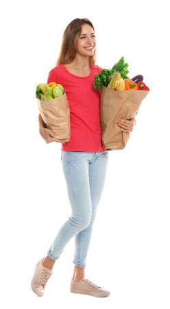 Young woman with bags of fresh vegetables isolated on white Banco de Imagens