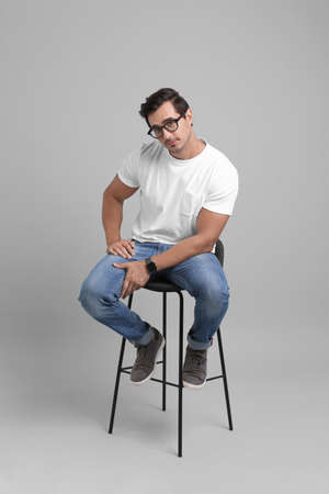 Handsome young man sitting on stool against grey background