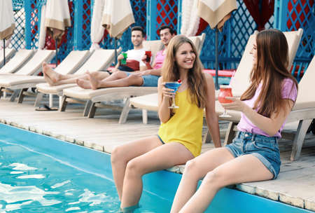 Happy young friends with fresh summer cocktails relaxing near swimming pool