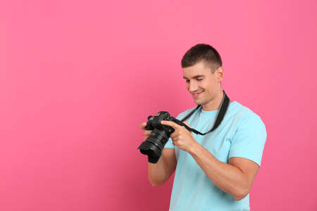 Young photographer with professional camera on pink background. Space for text