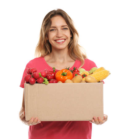 Young woman with box of fresh vegetables on white background