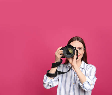 Professional photographer taking picture on pink background. Space for text Stock Photo