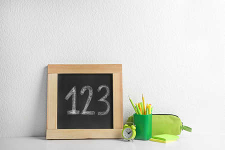 Small chalkboard with numbers and different school stationery on wooden table near white wall Standard-Bild