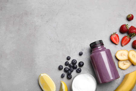 Bottle of acai drink and ingredients on grey background, flat lay. Space for text