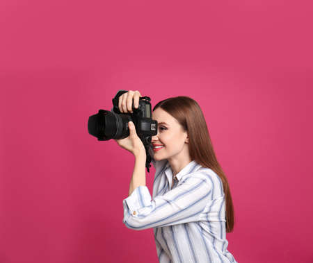Professional photographer taking picture on pink background