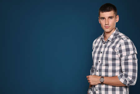 Portrait of handsome young man on blue background. Space for text