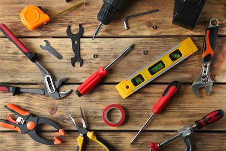Set of repair tools on wooden background, flat lay