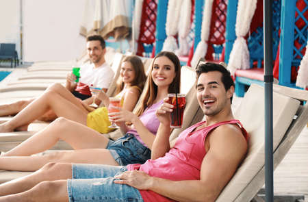 Happy young friends with fresh summer cocktails relaxing on sunbeds 写真素材
