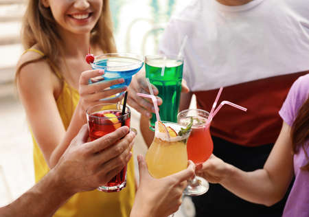 Friends clinking glasses with fresh summer cocktails outdoors, closeup