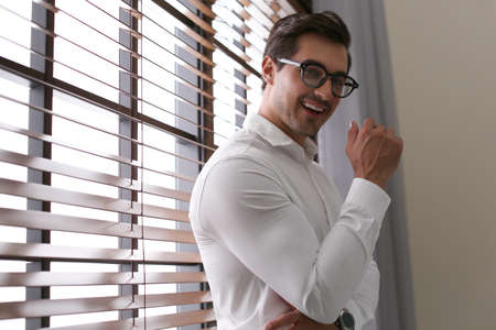 Handsome young man in white shirt with glasses standing near window indoors