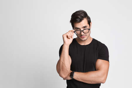 Portrait of handsome young man in black t-shirt with glasses on grey background. Space for text
