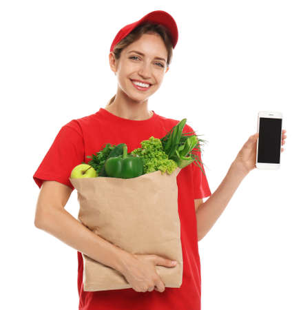 Delivery woman with bag of fresh vegetables and smartphone on white background, mockup for design