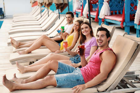 Happy young friends with fresh summer cocktails relaxing on sunbeds 版權商用圖片