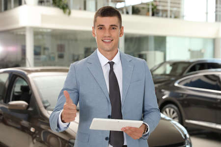 Young salesman with tablet in modern car dealership Stockfoto - 128598188