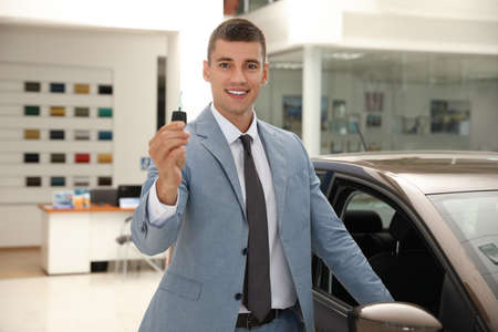 Young salesman with key near car in modern dealership Stockfoto
