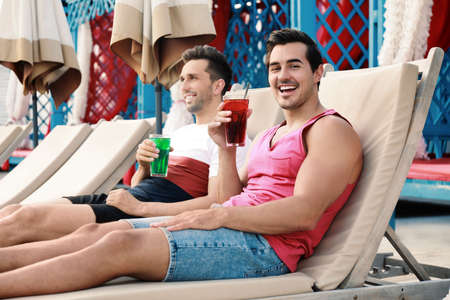 Happy young friends with fresh summer cocktails relaxing on sunbeds Imagens