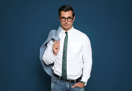 Portrait of handsome young businessman wearing glasses on blue background