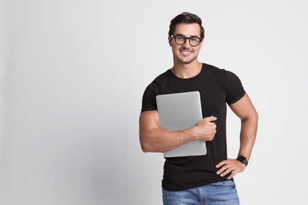 Handsome young man with laptop on grey background. Space for text Stock fotó
