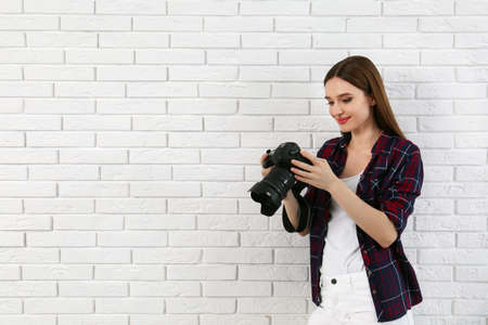 Professional photographer with modern camera near white brick wall. Space for text 版權商用圖片