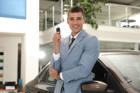 Young salesman with key near car in modern dealership Stockfoto - 128598201