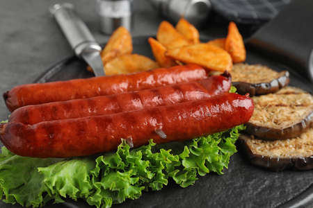 Delicious grilled sausages and vegetables on grey table, closeup