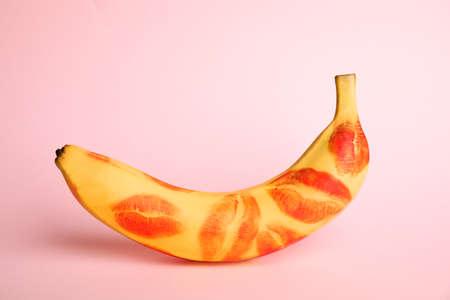 Plátano fresco con marcas de lápiz labial rojo sobre fondo rosa. Concepto oral