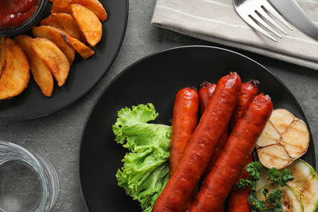 Delicious grilled sausages and vegetables on grey table, flat lay