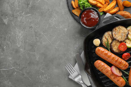 Delicious grilled sausages and vegetables on grey table, flat lay. Space for text Banco de Imagens