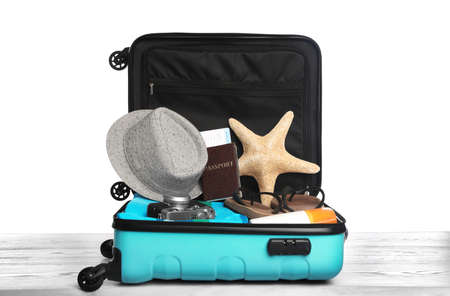 Open turquoise suitcase with different beach objects on wooden table, white background 版權商用圖片