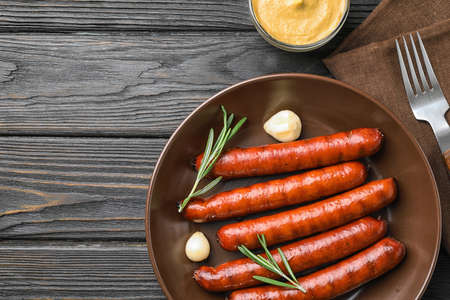 Flat lay composition with delicious grilled sausages on dark wooden table, space for text. Barbecue food Banco de Imagens