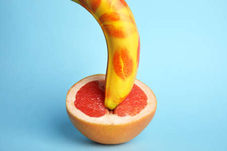 Fresh banana with red lipstick marks and grapefruit on blue background. Sex concept