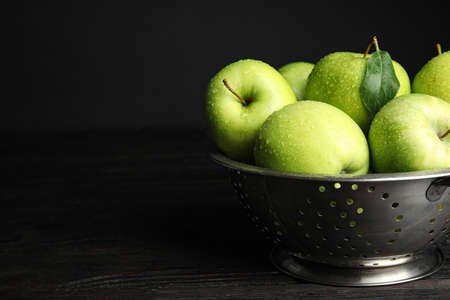 Colander of fresh ripe green apples on black wooden table, space for text 写真素材