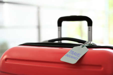 Stylish suitcase with travel insurance label on blurred background, closeup 版權商用圖片