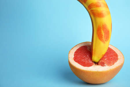 Fresh banana with red lipstick marks and grapefruit on blue background, space for text. Sex concept