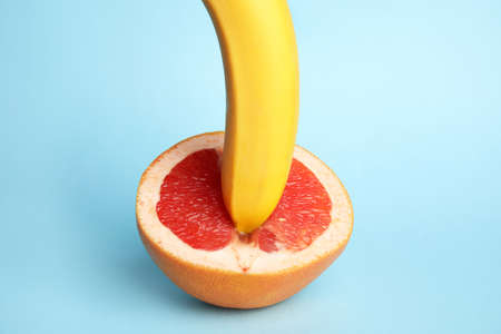Fresh grapefruit and banana on blue background. Sex concept Stock Photo