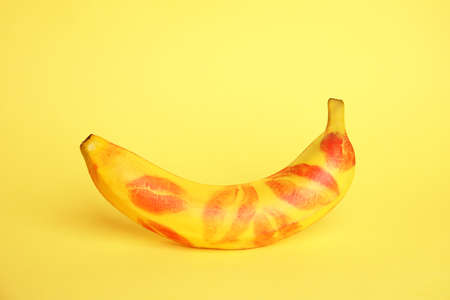 Fresh banana with red lipstick marks on yellow background. Oral concept