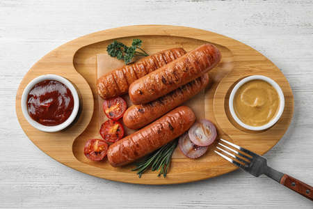 Delicious grilled sausages with sauces on wooden tray, top view. Barbecue food