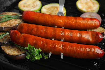 Delicious grilled sausages and vegetables   in grill pan, closeup