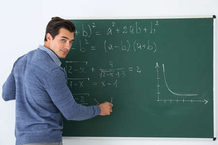 Young teacher writing math formulas on chalkboard in classroom Banque d'images