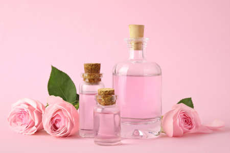 Flaschen ätherisches Öl und Rosen auf rosa Hintergrund Standard-Bild